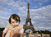 A baby being held aloft in front of the Eiffel Tower, Paris, France