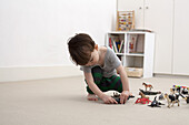 A little boy playing with some toy animal figurines on the floor of his bedroom
