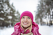 A beautiful woman in a knit cap looking up, outdoors in winter