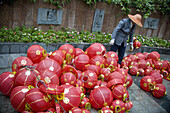 A worker considering a pile of Chinese lanterns