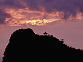 A pagoda on a hill in silhouette against a dramatic sky, Guilin River, Guilin, China