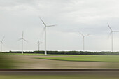 Wind turbines and landscape in blurred motion viewed from moving train