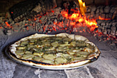 Potato and rosemary pizza baking in oven