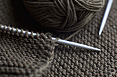 A pair of knitting needles, knitting and a ball of yarn, full frame