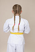 A girl wearing martial arts uniform with yellow belt, rear view