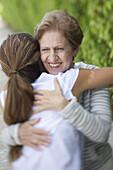 A senior woman hugging a young woman