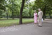 Senior couple contemplate hopscotch in the park