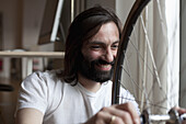 Smiling mid adult man repairing bicycle at home