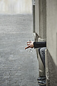Cropped image of woman holding cigarette and wineglass by sidewalk
