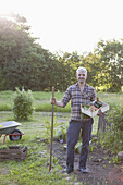 Full length of mature man carrying crate of freshly harvested vegetables at garden