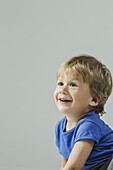 Smiling baby boy looking away over gray background