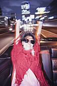 Blurred motion of happy woman enjoying car ride