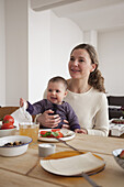 Smiling mother and baby girl looking away while sitting at table