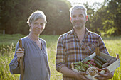 Portrait of mature couple with crate of freshly harvested vegetables at garden
