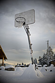 A basketball hoop in a snowy outdoor setting