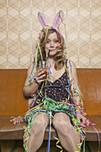 A tipsy woman drinking a cocktail and covered in streamers, portrait