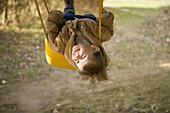 Baby girl swinging on swing, portrait