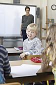 Boy sitting in classroom, smiling