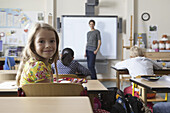 Girl sitting in classroom, smiling