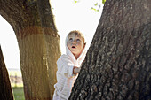 A young girl leaning on a tree trunk and looking up in wonder