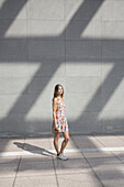 Young woman standing on pavement, looking away