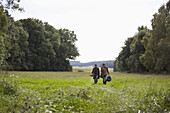 Young couple carrying camping accessories walking through field