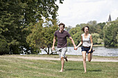 Young couple holding hands and running in park