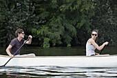Young couple rowing canoe on lake