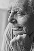 Thoughtful senior man with hand on chin looking away