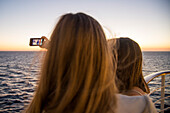 Two teenage girls taking a selfie photograph aboard cruise ship MS Deutschland (Reederei Peter Deilmann) at sunset, Atlantic Ocean, near Spain