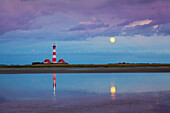 Lighthouse, thunder clouds and moon reflecting in the water, Westerhever lighthouse, Eiderstedt peninsula, Schleswig-Holstein, Germany