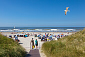Guests on their way to the beach, Norderney, Ostfriesland, Lower Saxony, Germany