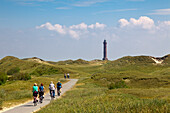 Cyclists on their way to the lighthouse, Norderney, Ostfriesland, Lower Saxony, Germany