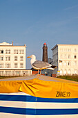 Seagull on a beach chair, lighthouse in the background, Borkum, Ostfriesland, Lower Saxony, Germany