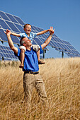 Solar park in summer, man carrying his son on his shoulders and are delighted by the sun, Lieschensruh, Edertal, Hesse, Germany, Europe
