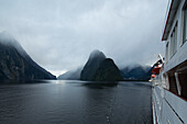 Side of expedition cruise ship MS Hanseatic (Hapag-Lloyd Cruises) in Milford Sound overcast with clouds, Milford Sound, Fiordland National Park, South Island, New Zealand