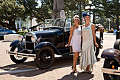 Art deco design: Two women in dresses from the twenties posing in front of a Ford Model A antique car, Napier, Hawke's Bay, North Island, New Zealand