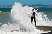 Happy woman standing by the sea and getting sprayed by a wave (MR), Napier, Hawke's Bay, North Island, New Zealand