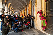 Venetian Carnival, tourism, masks, harlequin, jester, costume, posing, army of  photographers, arcade of Doge Palace, Venice, Italy