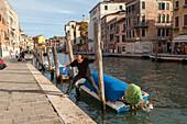 Fondamenta, boat moorings, motor boats, personal boats, canal, palina, paline, poles for mooring boats, man jumps from boat, Venice, Italy