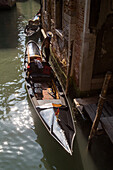 gondolier at mooring, waiting for tourists on his gondola in a narrow canal, old walls, boat, Venice, Veneto, Italy
