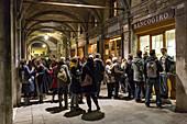 Night shot, bar, Campo San Giacometto, Rialto, young people drink under the arcades of a former historic bank, Banco Giro, Venice, Italy