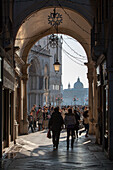 view through arcade towards St Mark's Square, San Marco, back lighting, silhouettes of people, tourists, Venice, Italy