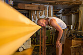 assistant Pietro Meneghini inspects a timber oar in the workshop of Venetian forcola and oar maker Saverio Pastor, craftsman, art object, Venice, Italy
