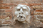 sculpture, stone relief of male head, open mouth and eyes, desperate, brickwall, Venice, Italy