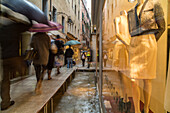 Tourists with umbrellas and plastic covered shoes, rubber boots, walk on passarelle, walkways during Acqua alta fashion shop near St Mark's Square, San Marco, passarelle, high water caused by Sirocco wind and full moon, rain in Venice, Italy