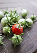 Green and red cherry tomatoes on wooden table