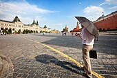 Moscow, Russia-July 20, 2010:An executive crosses the Red Square in Moscow with an umbrella shielding the intense heat of July and a little rain.