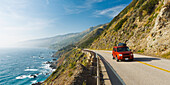 California, Big Sur, Coastal Shot Of Highway 1 With Red Vehicle Driving