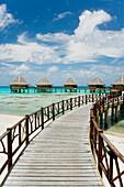French Polynesia, Tuamotu Islands, Rangiroa Atoll, Boardwalk Leading To Luxury Resort Bungalows Over Ocean.